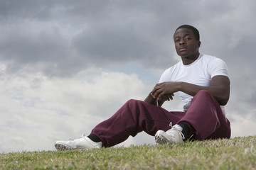 African man sitting on grass