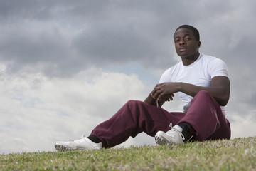 African man sitting on grass