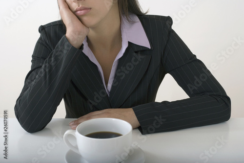 Mixed race businesswoman drinking coffee