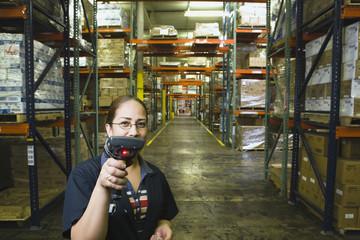 Hispanic woman holding scanner in warehouse