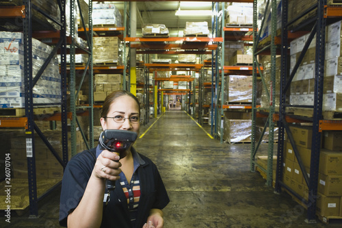 Hispanic woman holding scanner in warehouse