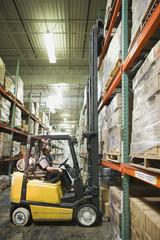 Hispanic man operating forklift in warehouse