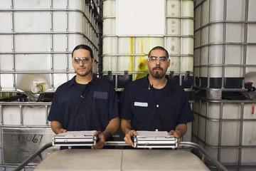 Hispanic men smiling in manufacturing plant
