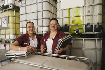 Hispanic women smiling in manufacturing plant