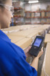 Hispanic woman using tracking device in warehouse
