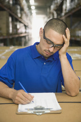 Hispanic man completing paperwork in warehouse
