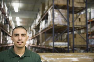 Hispanic man smiling in warehouse