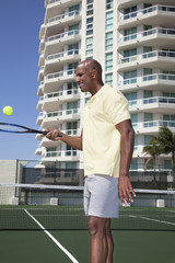 African man balancing tennis ball on racket
