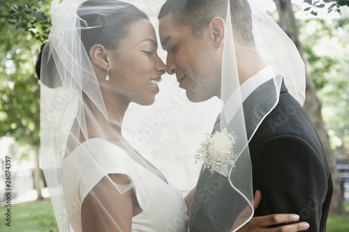 Bride and groom hugging under veil