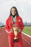 Mixed race track & field athlete wearing medals and holding trophy