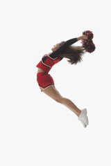 Mixed race cheerleader jumping with pom-poms