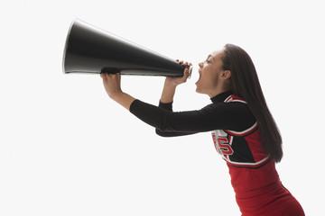 Mixed race cheerleader yelling into megaphone
