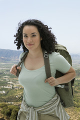 Smiling Hispanic woman wearing backpack