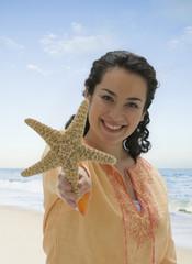 Smiling Hispanic woman holding starfish on beach
