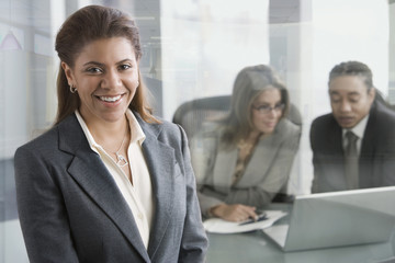 Smiling businesswoman with co-workers in background