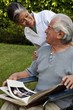 Home nurse and elderly man looking at photograph album
