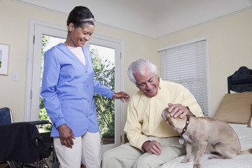Home nurse and elderly man petting dog on bed