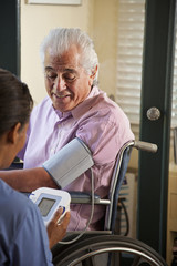 Home nurse taking elderly man's blood pressure