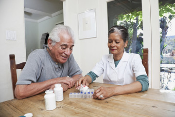 Home nurse filling daily vitamin container for elderly man