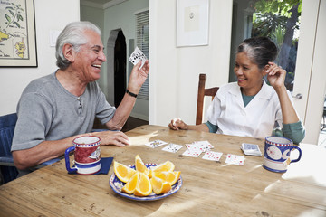 Home nurse and elderly man playing cards