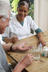 Home nurse giving elderly man vitamins