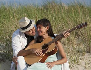 Hispanic couple playing guitar on beach