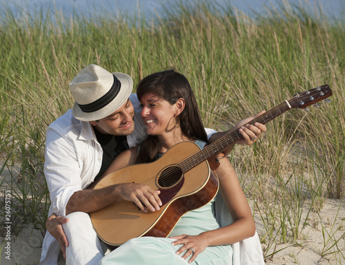 Hispanic couple playing guitar on beach