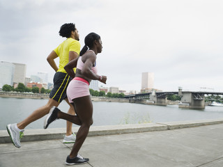 Couple running along urban waterfront