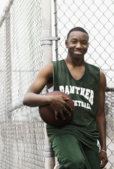 Smiling African basketball player holding ball against fence