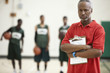 Serious African basketball coach holding clipboard in gym
