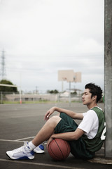 Mixed race basketball player sitting with ball under basket