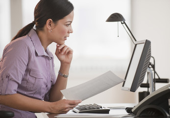 Hispanic businesswoman working at computer in office