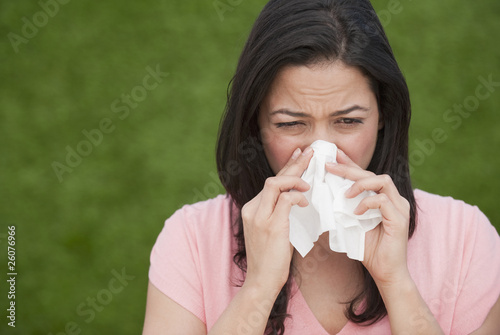 Hispanic woman blowing nose