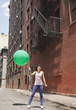 Mixed race woman holding balloon on urban street