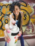Mixed race graffiti artist holding spray paint can
