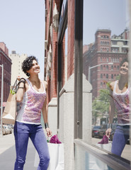Mixed race woman window shopping on urban street