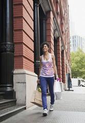 Mixed race woman carrying shopping bag on urban sidewalk