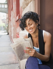 Mixed race woman reading classified ads on urban street