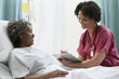 African nurse talking with hospital patient