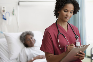 African nurse writing on medical chart in hospital room