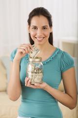 Hispanic woman putting money in jar
