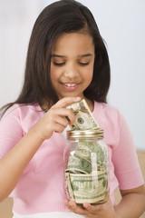 Hispanic girl putting money in jar