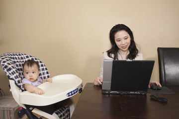 Chinese mother working on laptop next to baby in high chair