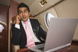 Middle Eastern businessman using laptop and cell phone on private jet