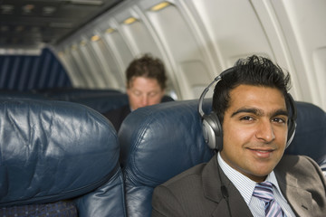 Middle Eastern businessman listening to headphones on airplane