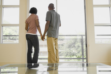 African couple holding hands and looking out balcony window