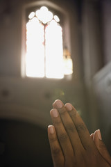 Light from church window shining on hands clasped in prayer