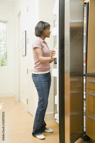 African woman looking in refrigerator