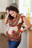 Pregnant Hispanic woman frowning in kitchen
