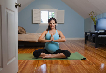 Pregnant Hispanic woman practicing yoga
